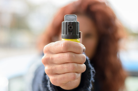 Close up of pepper spray in hand of partially obscured red haired woman standing outside Archivio Fotografico