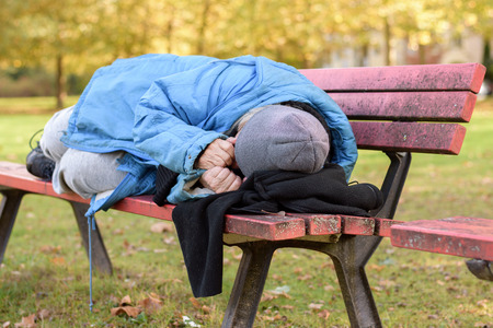 indigent: Homeless elderly woman sleeping rough in a park curled up against the cold autumn weather on a rustic wooden bench