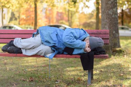 mujer mayor sin hogar durmiendo en la calle en un parque acurrucado contra el frío del otoño en un banco de madera rústica Foto de archivo