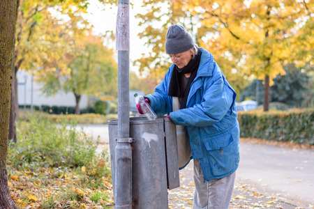 indigent: Indigent senior woman scrounging through a bin for food on an urban autumn street in a concept of homelessness and poverty