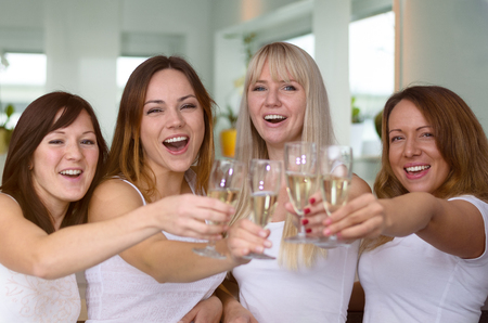 partying: Four merry women partying and toasting with flutes of champagne laughing as they celebrate a special occasion, holiday or success, close up upper bodies