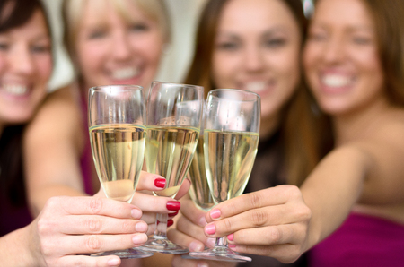 Young ladies toasting a special occasion together with flutes of champagne clinking glasses for the camera, close up selective focus view Stock Photo
