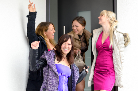 evening wear: Happy laughing group of stylish young women in evening wear posing in an open doorway waving and grinning at the camera