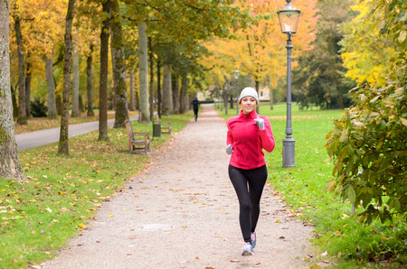 Attractive shapely young woman out jogging in a colorful autumn park approaching along a footpath in a healthy active lifestyle and fitness concept