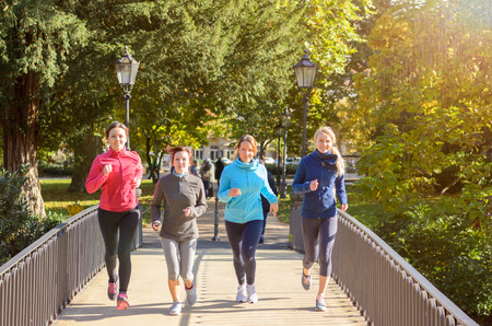 sweatshirts: Four beautiful Caucasian young women in different colored sweatshirts jogging over bridge