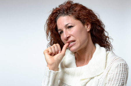 speculative: Thoughtful young woman chewing her thumb nail as she looks pensively at the camera with her head tilted to the side, isolated on white