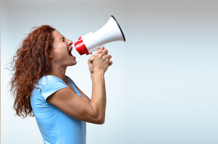 Young woman shouting into a megaphone, side view on white conceptual of a rally or protest