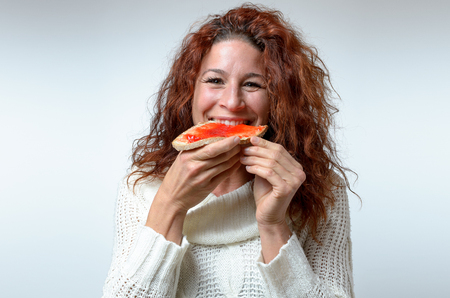 grins: Smiling happy woman biting into colorful red berry jam on a slice of bread as she grins at the camera, close up head and shoulders on white