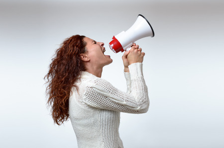 authoritative woman: Young woman shouting into a megaphone, side view on white conceptual of a rally or protest