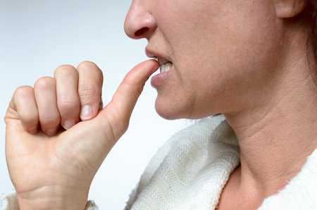 contemplation: Young woman biting her thumb nail in anxiety or contemplation, close up partial face view in profile over white