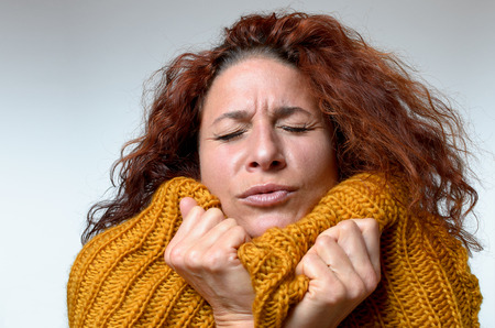 Cold young woman snuggling into a warm knitted woollen winter top with a grimace and her eyes closed as she tries to warm up, close up on white