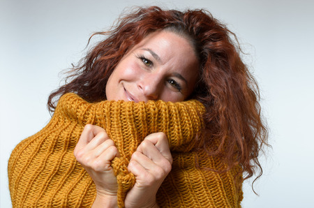 snuggling: Warm happy woman snuggling into the high collar of a warm woolly winter jersey with a charming smile of pleasure isolated on white