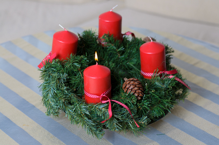 Traditional festive evergreen pine or fir wreath to celebrate the Christmas and Advent holiday season with burning red candles and natural cones and foliage in a close up high angle view