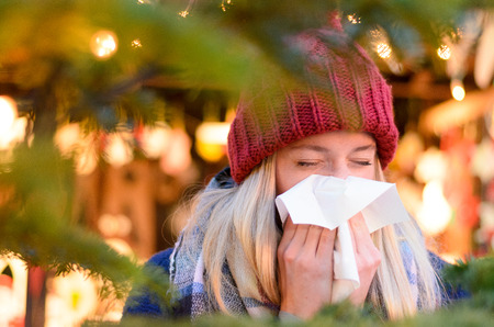 Young woman outdoors at night attending a colorful Christmas market blowing her nose on a tissue n a concept of health, sickness and seasonal colds and flu Foto de archivo
