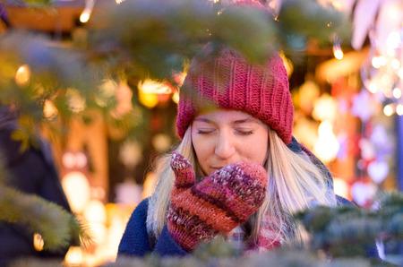 tosiendo: mujer joven fría toser en sus manos enguantadas mientras se está al aire libre en una noche de invierno en un mercado de Navidad Foto de archivo