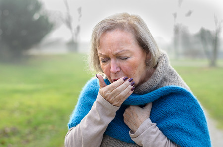 Elderly stylish attractive blond woman coughing or sneezing into her hand as she stands on a rural lane on a misty winter day