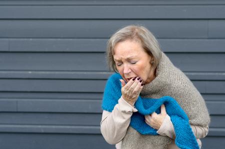 コピー スペースを持つ金属の背景灰色の季節気管支炎やインフルエンザ、医療ヘルスケアの概念で彼女の胸を握りしめながら彼女の手に咳エレガン