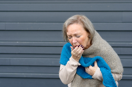 Elegant senior woman coughing into her hand while clutching her chest in a concept of seasonal bronchitis or influenza and medical healthcare, grey metal background with copy space