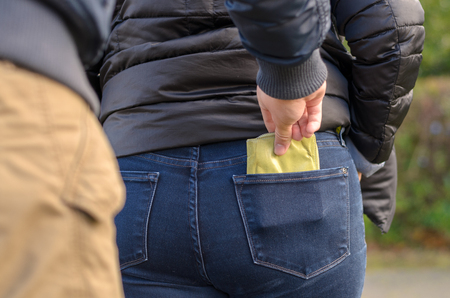 Pickpocket stealing a purse from the back jeans pocket of a woman walking outdoors on a road, close up view of his hand Stock Photo