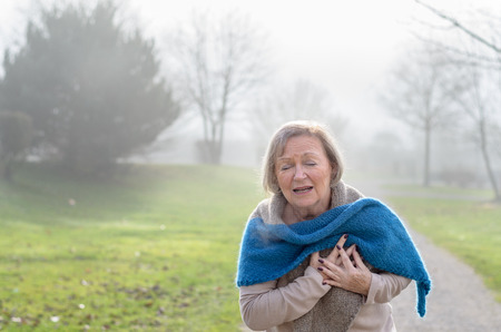 Senior dame klemde haar borst van de pijn bij de eerste tekenen van angina of een hartinfarct of een hartaanval, het bovenlichaam op een landelijke rijstrook op een mistige winterdag