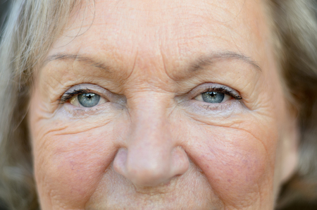 Close up on the aged and wrinkled face of an attractive senior woman with lovely blue eyes and greying blond hair