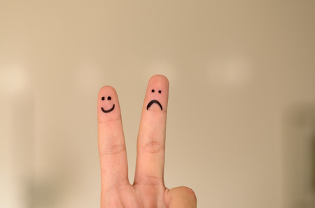 morose: Two hand drawn emoticon faces on a persons fingers , one happy and smiling and the other unhappy, sad or depressed isolated on a neutral background with copy space