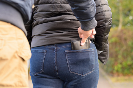 Pickpocket stealing a purse from the back jeans pocket of a woman walking outdoors on a road, close up view of his hand Foto de archivo