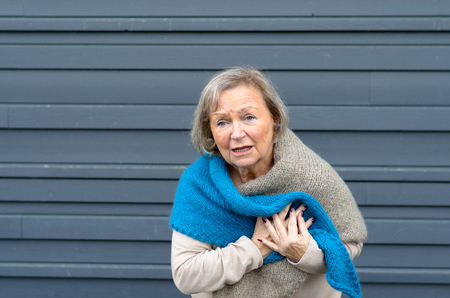 infarct: Senior lady clutching her chest in pain at the first signs of angina or a myocardial infarct or heart attack, upper body on grey metal door background with copy space
