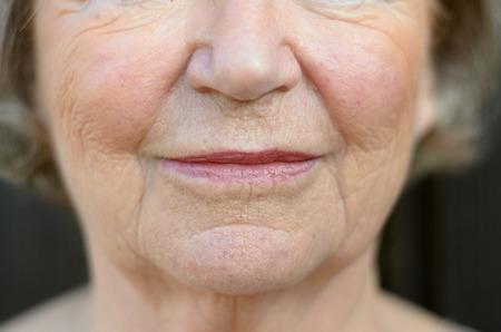 Close-up op de mond van een senior blonde vrouw met haar mond gesloten en een ernstige uitdrukking Stockfoto