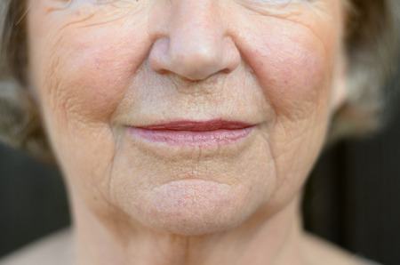 Closeup on the mouth of a senior blond woman with her mouth closed and a serious expression