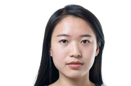 白で隔離レンズを直接見て髪の長い穏やかな魅力的な若い中国女性のヘッド ショット 写真素材