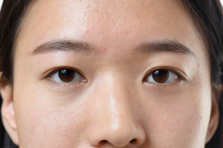 expressionless: Close up cropped view of the calm dark brown eyes of a young Chinese woman looking directly into the camera Stock Photo