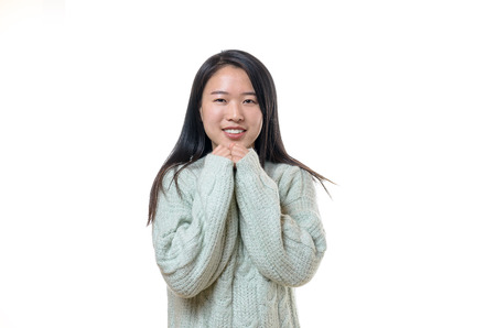 Pretty young Chinese woman in winter fashion wearing a thick woolly jersey tucking her hands into the sleeves and raising them to her throat as she smiles at the camera