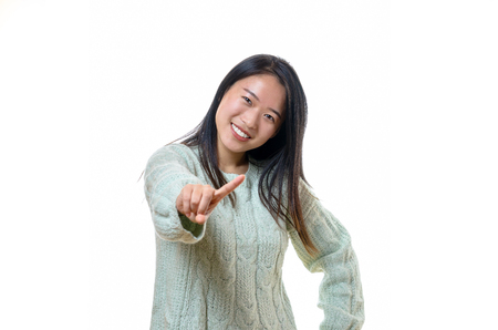 disapproving: Cute young Chinese woman wagging her finger at the camera admonishing the viewer with a sweet friendly smile, isolated on white