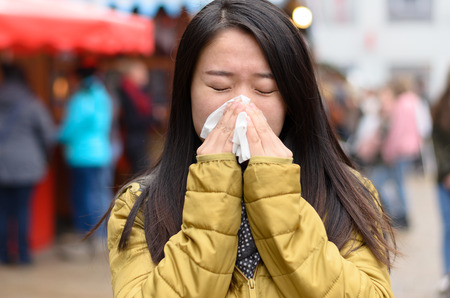 Young Chinese woman blowing her nose on a cold winter night outdoors as she attends a Christmas market viewed behind the branch of a natural evergreen Xmas tree in a concept of health and seasonal flu Stock Photo