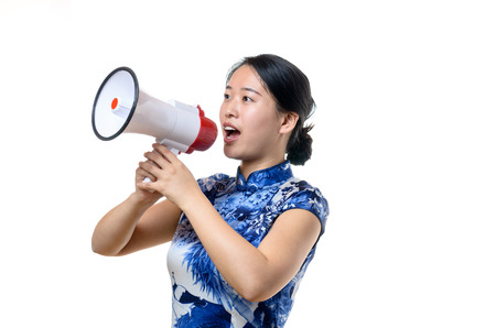 addressing: Attractive Chinese woman in traditional dress shouting into a loud hailer or megaphone at a rally or demonstration or when addressing a crowd public speaking, isolated on white Stock Photo