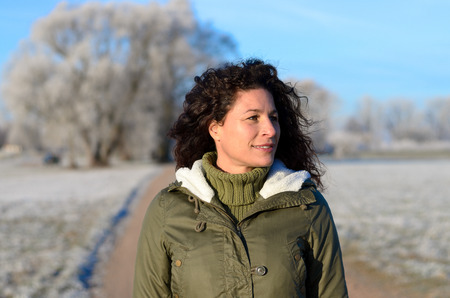 Pretty woman walking along a rural road through open fields coated with white rime or hoar frost on a freezing cold sunny winter day in an active lifestyle and weather concept