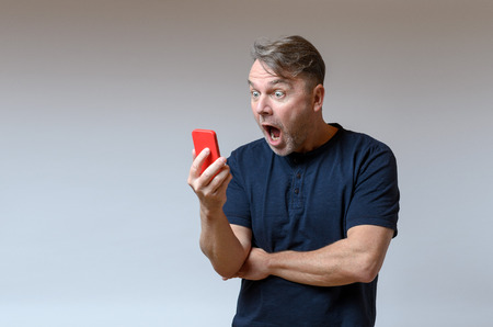 agape: Middle-aged man standing looking at his mobile in shock and horror with wide eyes and his mouth agape as he stares at a message on the screen, isolated on grey with copy space Stock Photo