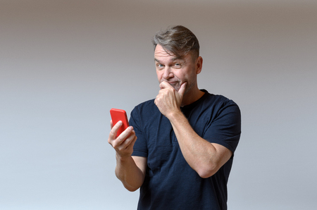speculative: Thoughtful man with his hand to his mouth holding a mobile phone in his hand looking at the camera as though for affirmation with a speculative expression, isolated on grey Stock Photo