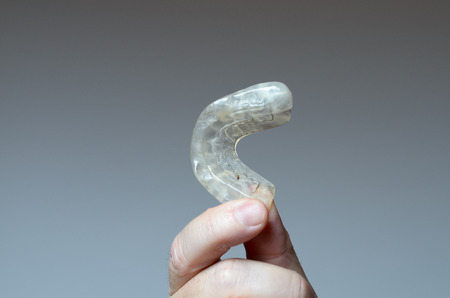 Finger holding a bite plate to protect his teeth at night from grinding caused by bruxism