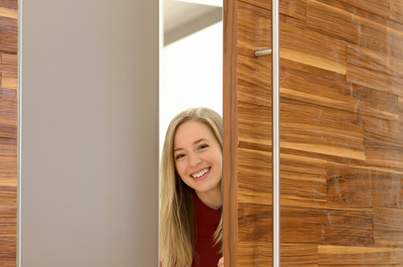 changing room: Smiling woman looking out of a changing room door at a clothing store or boutique as she shops for clothes Stock Photo