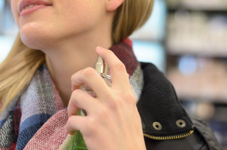 atomiser: Young woman in a warm woolly knitted winter scarf spraying her neck with perfume in a store as she shops for Christmas