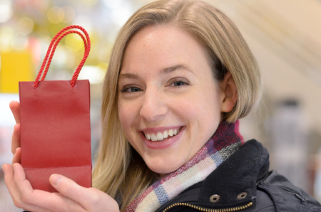 displaying: Happy woman displaying a small Christmas gift in a festive red store carrier bag with a warm friendly smile, close up head and shoulders Stock Photo