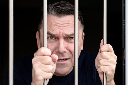 incarcerated: Middle aged blue eyed man incarcerated and wearing blue shirt stands holding prison bars