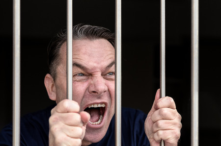 incarcerated: Middle-aged man kept captive in a prison cell grabbing the bars and yelling his frustration, desire to be free and defiance at the top of his voice, close up on his hands and face Stock Photo