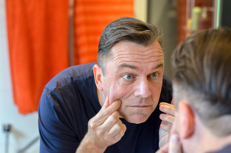 Middle aged caucasian man stands at mirror and pinches his face while wearing a blue shirt Stock Photo