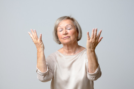 Senior woman with her hands up to the sky, standing with eyes closed on plain grey background Stock Photo