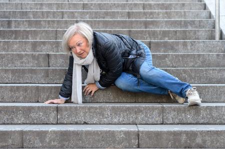 Senior woman accidentaly falling down stone steps outdoors Foto de archivo