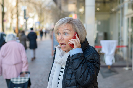 Senior woman with grey hair is being shocked while talking by the phone standing outside in the street with passers blurred in background, looking away with her mouth open