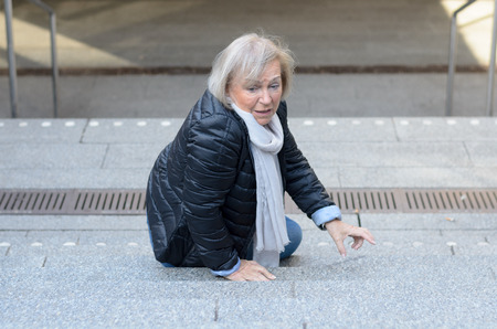 overthrown: Helpless senior woman falling down steps and looking irritated